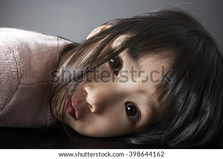 Closeup portrait of Asian little girl, Lying on the table - stock photo