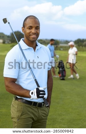 Closeup portrait of athletic young male golfer with golf club, smiling, looking at camera. - stock photo