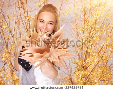 Closeup portrait of attractive blond female having fun in autumn park, holding in hand beautiful bouquet of dry maple foliage - stock photo