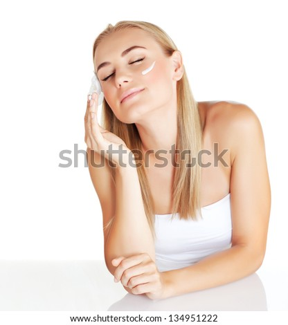 Closeup portrait of attractive blond female using moisturizer isolated on white background, cute girl enjoying day spa with closed eyes, pleasure concept