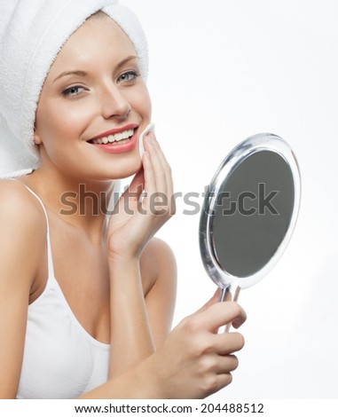 closeup portrait of attractive  caucasian smiling woman blond isolated on white studio shot lips toothy smile face towel applying cream head and shoulders looking at camera blue eyes tooth - stock photo