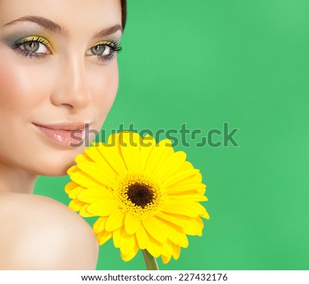 closeup portrait of attractive  caucasian smiling woman brunette isolated on white studio shot lips face closeup skin makeup eyes  head and shoulders looking at camera yellow flower - stock photo