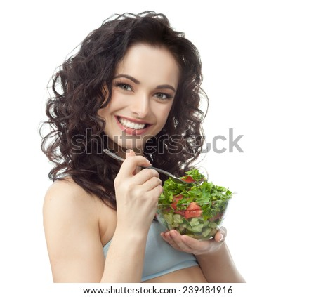 closeup portrait of attractive  caucasian smiling woman brunette isolated on white studio shot lips toothy smile face hair head and shoulders looking at camera tooth eating salad - stock photo
