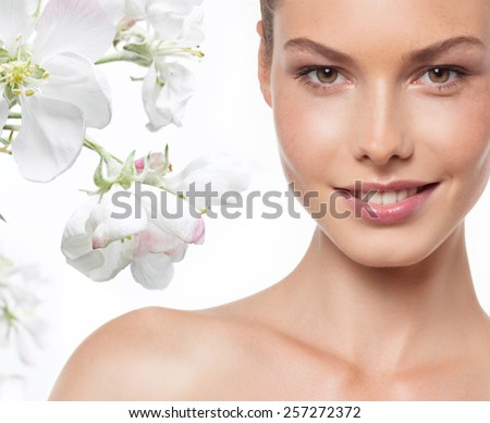 closeup portrait of attractive  caucasian smiling woman brunette isolated on white studio shot lips toothy smile face head and shoulders looking at camera tooth spring flowers - stock photo