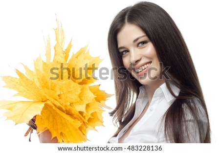 closeup portrait of attractive  caucasian smiling woman brunette isolated on white studio shot lips toothy smile face hairlooking at camera tooth hand holding yellow marple autumn leaves
