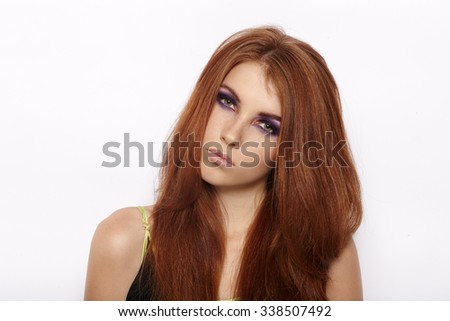 Closeup portrait of attractive cute redhead woman with violet smokey eyes makeup looking into camera isolated
