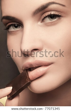 closeup portrait of attractive female with dark chocolate - stock photo