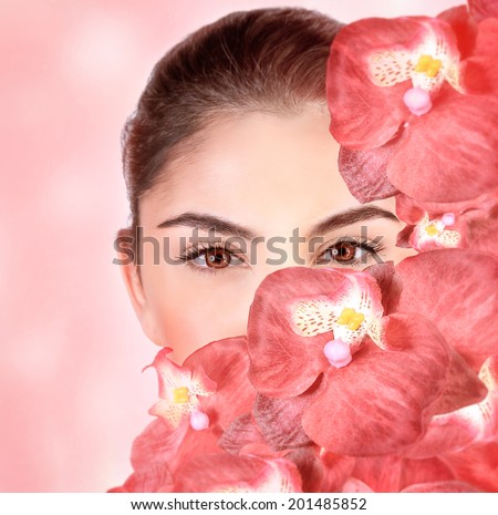 Closeup portrait of attractive girl cover part of face with fresh orchid flowers, isolated on pink background, luxury spa salon, wellness concept - stock photo
