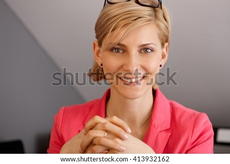 Closeup portrait of attractive young blonde businesswoman, smiling, looking at camera. - stock photo