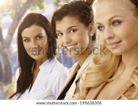 Closeup portrait of attractive young businesswomen outdoors, smiling happy. Selective focus. - stock photo