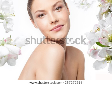 closeup portrait of attractive young caucasian smiling woman brunette isolated on white studio shot lips face head and shoulders looking at camera  spring flowers - stock photo