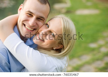 Closeup portrait of attractive young couple outdoors at dusk. - stock photo