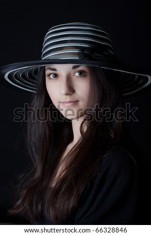 Closeup portrait of attractive young woman in a hat  on a dark background - stock photo