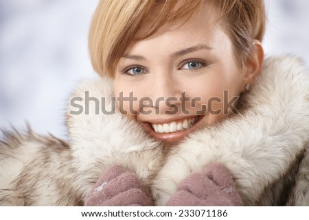 Closeup portrait of attractive young woman wearing warm fur coat in winter. - stock photo