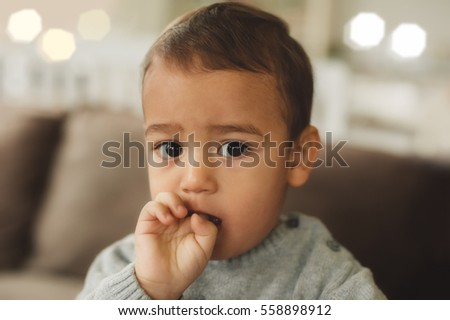 Closeup portrait of baby boy with finger in the mouth, adorable sweet child