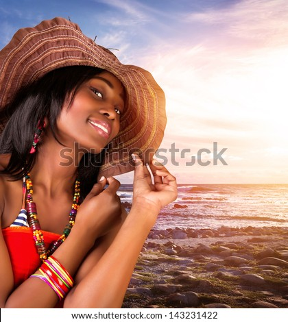 Closeup portrait of beautiful african woman on the beach, sexy model posing on seashore on sunset, wearing stylish hat and fashionable accessories, summer vacation - stock photo