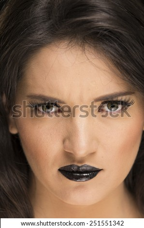 closeup portrait of beautiful angry young woman wearing goth makeup - stock photo