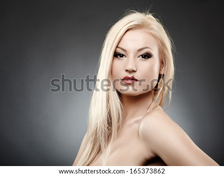 Closeup portrait of  beautiful blonde over gray background - stock photo