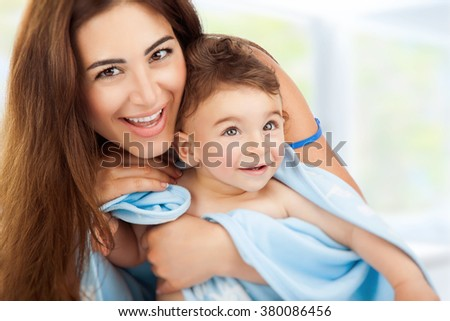 Closeup portrait of beautiful cheerful mother holding on hands cute little son after bath wrapped in towel, child's hygiene, happy healthy lifestyle - stock photo
