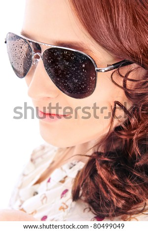 Closeup portrait of beautiful fashion woman wearing sunglasses over a white background