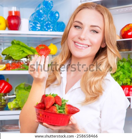 Closeup portrait of beautiful female eating strawberry, open fridge full of fruits and vegetables, dieting and healthy eating concept - stock photo