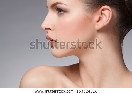 closeup portrait of beautiful female face over gray background - stock photo
