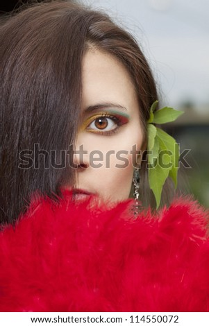 Closeup portrait of beautiful girl with face closed by fan - stock photo