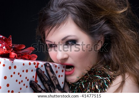 Closeup portrait of beautiful girl with red lips, tinsel and present on black