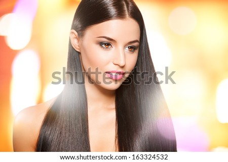 closeup portrait of beautiful girl with straight long dark hair against shining yellow background  - stock photo