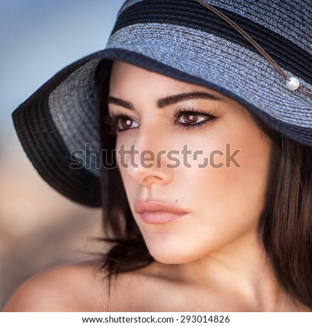 Closeup portrait of beautiful gorgeous woman wearing stylish sun hat, perfect makeup, seriously looking on a side, fashion and beauty