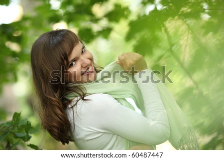 Closeup portrait of beautiful happy young woman in green scarf outdoors, smiling. Shallow DOF.