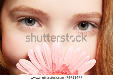 closeup portrait of beautiful healthy redhead teen girl with gerbera flower - stock photo