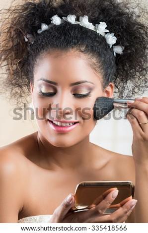 Closeup portrait of beautiful hispanic bride applying blush makeup on - stock photo