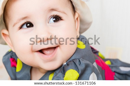 Closeup portrait of beautiful smiling baby girl in hat - stock photo