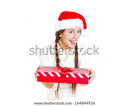 Closeup portrait of beautiful smiling happy young woman wearing red santa claus hat giving present wrapped in ribbon to you, camera gesture. Positive human emotion facial expression. Season greetings - stock photo