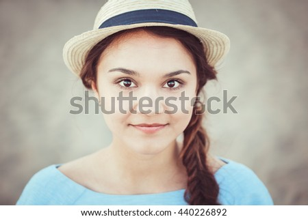 Closeup portrait of beautiful smiling white Caucasian brunette girl with brown eyes and plait, in blue dress and straw hat, looking in camera, rustic retro vintage style concept - stock photo