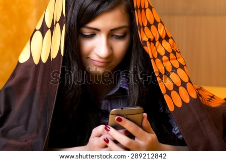 Closeup portrait of beautiful teenage girl using mobil phone hidden under the colorful sheet  in her bedroom - stock photo