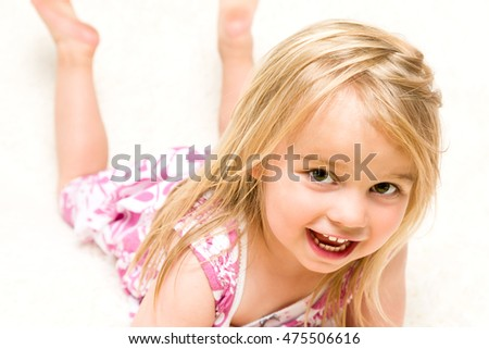 Closeup Portrait of Beautiful Toddler Girl Lying Down on Neutral Background