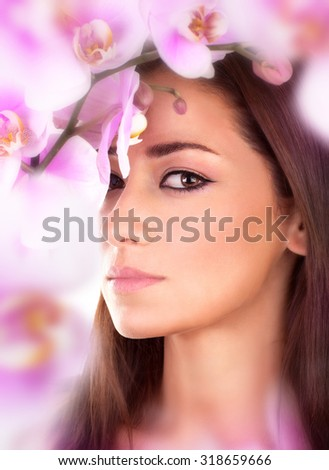 Closeup portrait of beautiful woman in amazing fresh orchid garden, gentle pink flowers around cute female face, enjoying day spa - stock photo