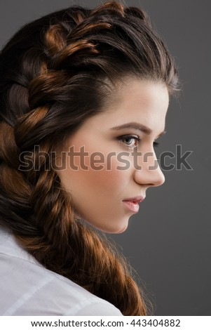 Closeup portrait of beautiful woman posing for photographer while demonstrating her modern hairstyle in studio. Hair braids concept.