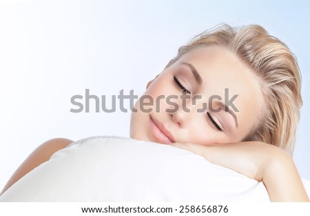 Closeup portrait of beautiful woman sleeping on the pillow isolated on blue and white background, happy calm day dreaming, conception of relaxation