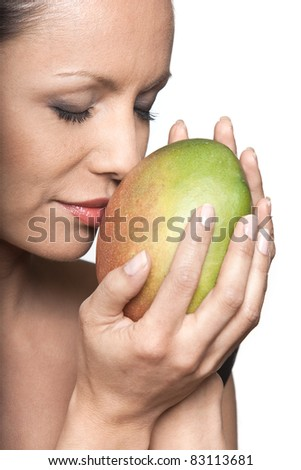 Closeup portrait of beautiful woman smelling fresh mango with eyes closed in studio isolated on white background - stock photo