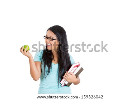 Closeup portrait of beautiful woman student or teacher with eyeglasses holding books on one arm and green apple in other hand, isolated on white background with copy space - stock photo