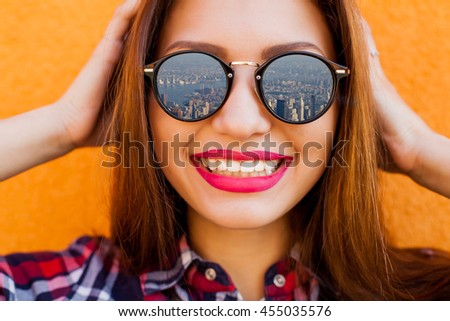 Closeup portrait of beautiful women with perfect make-up and sunglasses with reflection, smiling. Concept target, dream. Archive a goal. Orange background - stock photo