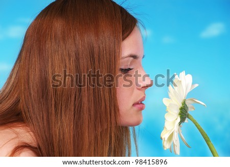 Closeup portrait of beautiful young female smelling a flower - stock photo