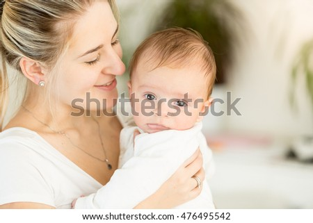 Closeup portrait of beautiful young mother holding her baby on hands