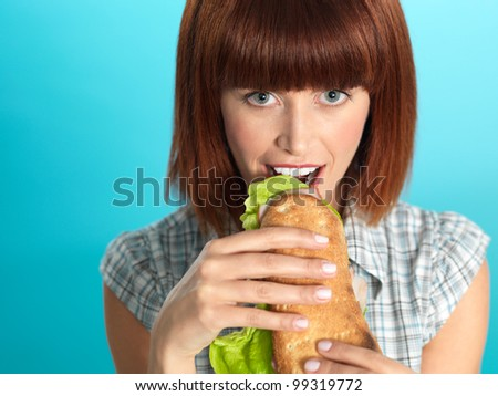 closeup portrait of beautiful young woman, eating a big sandwich, smiling, on blue background - stock photo
