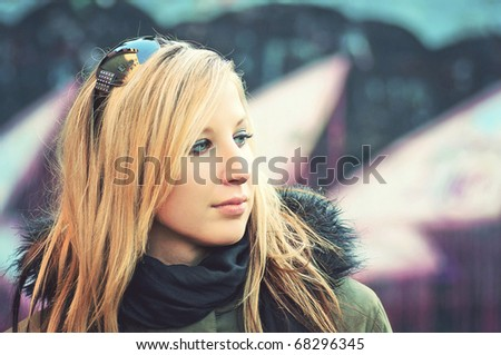closeup portrait of beautiful young woman standing by the road in front of graffiti wall - stock photo
