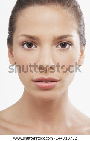 Closeup portrait of beautiful young woman with blank expression over white background - stock photo