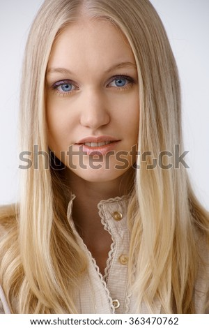 Closeup portrait of beautiful young woman with long blonde hair and blue eyes. - stock photo